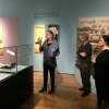 Tour leader talking about exhibit to group in foreground.