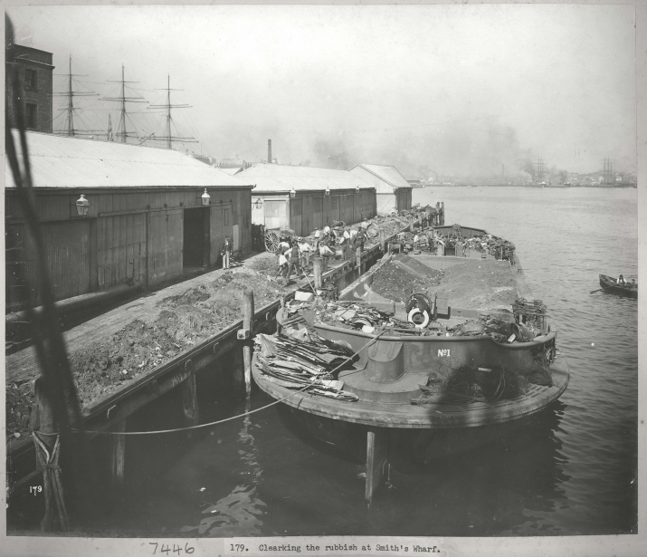 Black and white photograph of barge alongside wharf.
