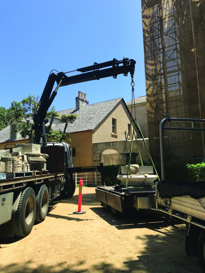 Crane lifting carved stonein front of scaffolding and house in background.