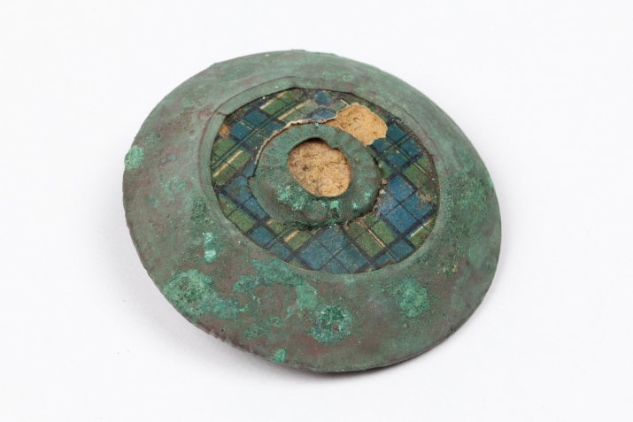 Copper brooch with green patina, green and blue check central inlay.