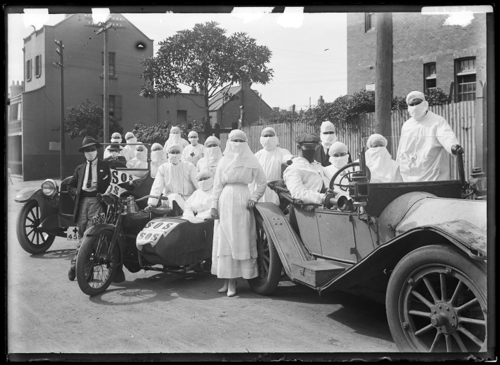 Nurses in masks standing next to a car