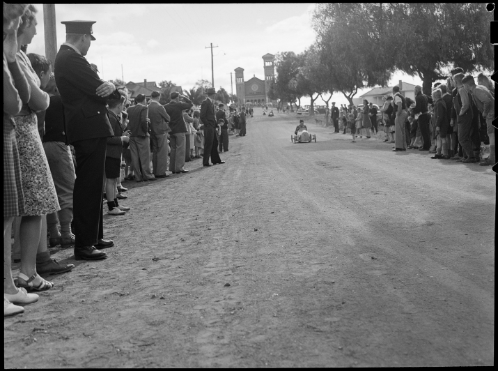 Black and white photo of people lining empty road.