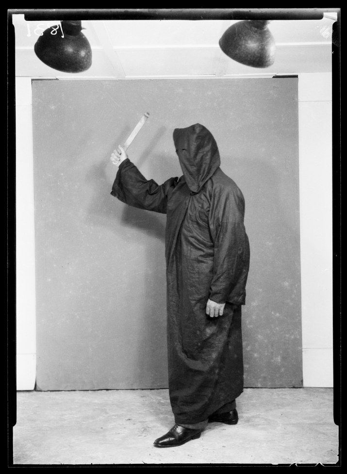 Black and white image of person in black robe and hood, wielding a weapon.