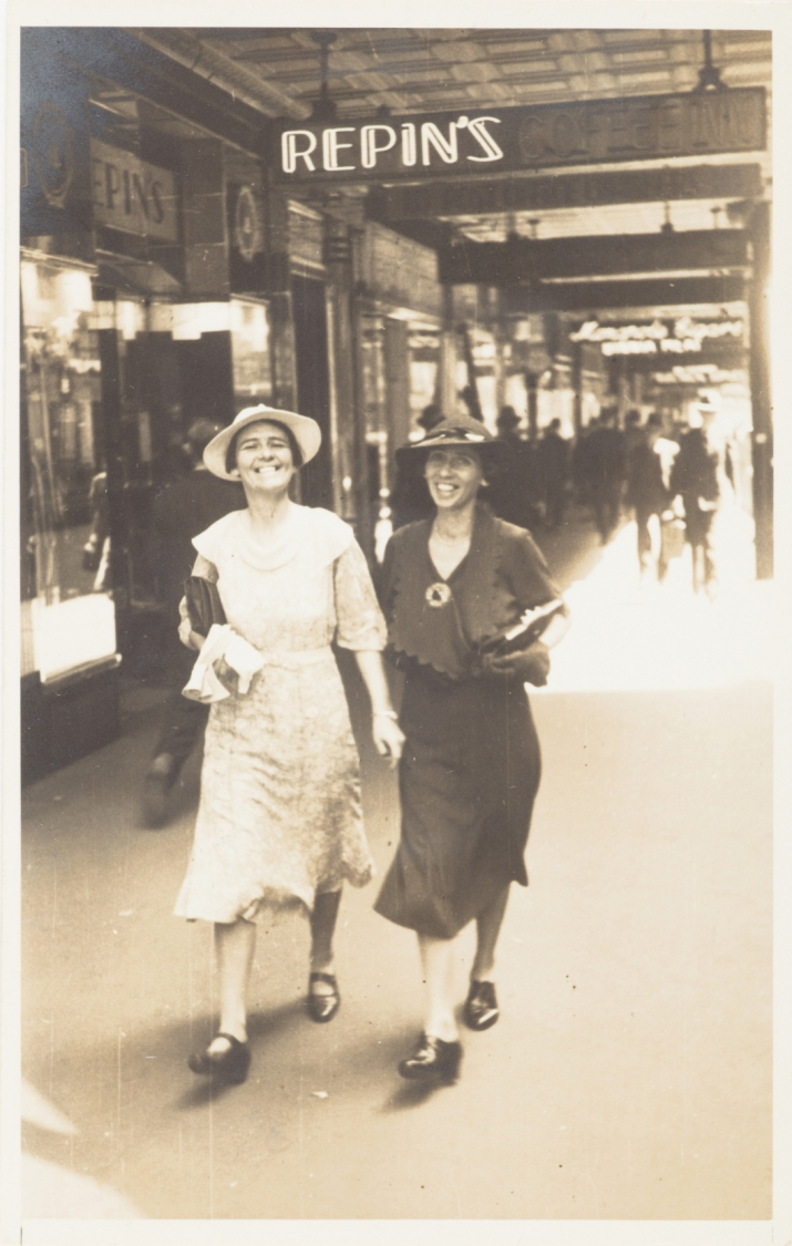 Sepia toned black and white photo of two women in hats walking down street.