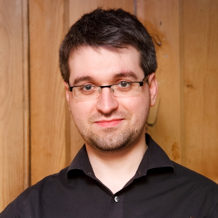 Portrait of man in glasses with black shirt.