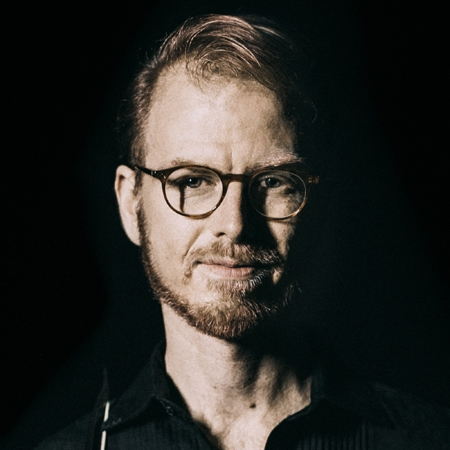 Portrait of man with glasses and trim beard against black background.