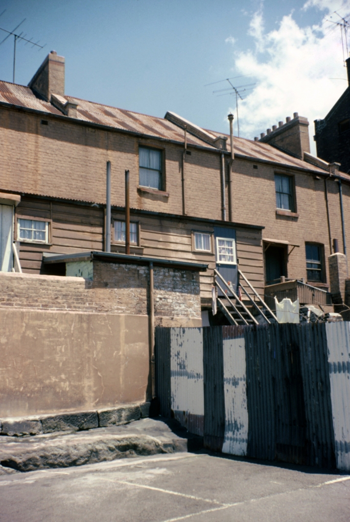 Back view of row of terrace houses showing fences and yards.