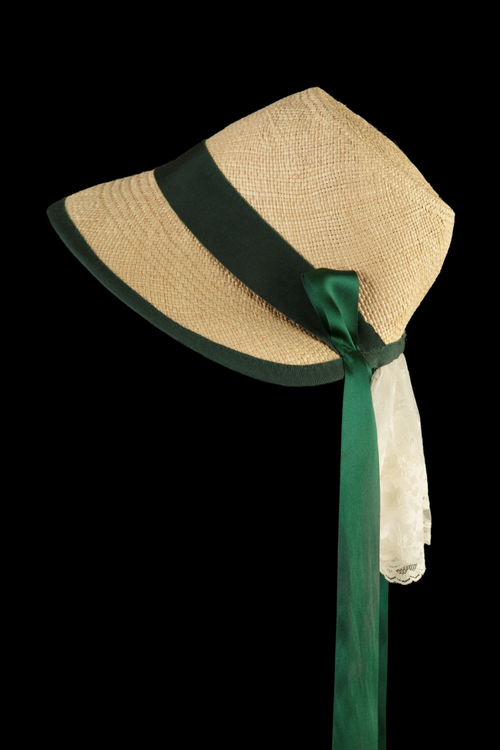 Reproduction of a mid nineteenth century cottage bonnet with green ribbon.