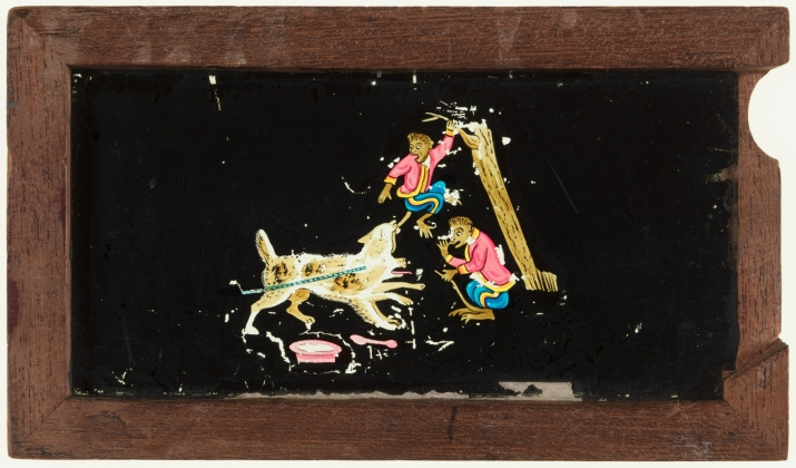 A timber framed glass magic lantern slide featuring a hand-drawn and coloured image of a monkey and a chained dog. A secondary sliding glass plate is missing and the image is damaged.