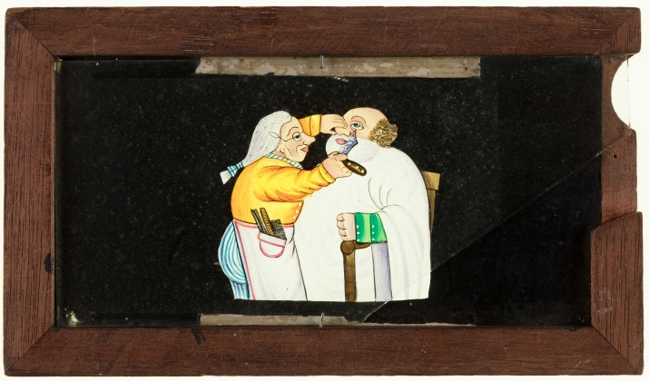 A timber framed, glass magic lantern slide featuring a hand drawn and coloured image of a man being shaved. A secondary sliding glass plate provides movement of the barber's arm and razor.