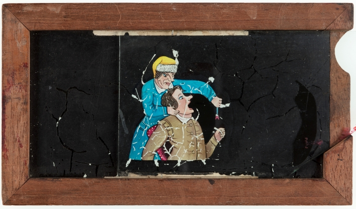 A timber framed glass magic lantern slide featuring a hand-drawn and coloured image of a dentist pulling a tooth. A secondary sliding glass plate provides before and after images of the extraction.
