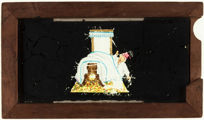 A timber framed glass magic lantern slide featuring a hand-drawn and coloured image of a man falling out of bed. The frame is stamped with manufacturer's details and the slide title is inscribed on the top edge in black ink.