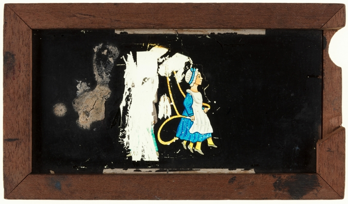 A timber framed, glass magic lantern slide featuring a hand-drawn and coloured image of a girl skipping rope. A secondary sliding glass plate is missing. The frame is stamped with the manufacturer's details and slide title is inscribed on top in black.
