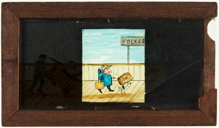 A timber framed, glass magic lantern slide featuring a hand drawn and coloured image of a man with dog and luggage on Folkestone railway platform. A secondary sliding glass plate depicts the man being knocked off his feet.