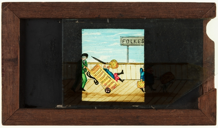 A timber framed, glass magic lantern slide featuring a hand drawn and coloured image of a man with dog and luggage on Folkestone railway platform being knocked off his feet. The frame is stamped with manufacturer's details and the slide title is inscribed