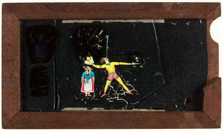 A timber framed glass magic lantern slide featuring a hand-drawn and coloured image of a male acrobat juggling an old woman, a ball and a broom(?). The framed is stamped with the manufacturer's details and the slide title is inscribed on the top edge in b