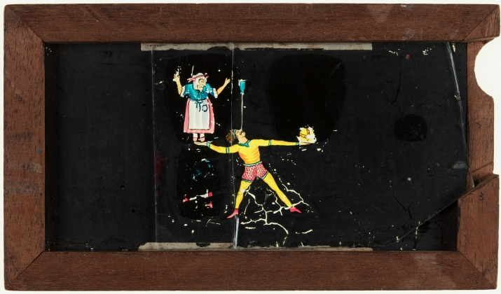 A timber framed glass magic lantern slide depicting man balancing old woman on his outstretched hand. The frame is stamped with the manufacturer's details and the slide title is inscribed on the top edge in black ink.