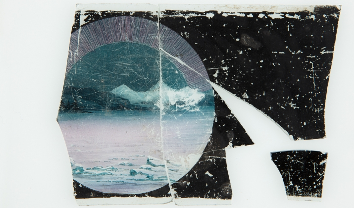A broken glass panel from magic lantern slide featuring a hand-drawn and coloured image of an ice field with a representation of the aurora borealis in the sky above mountains. The slide is broken into five pieces with some sections missing.