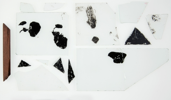 One section of timber slide frame and fourteen fragments of glass from magic lantern slides, some featuring areas of black paint used to alter the slide scene.