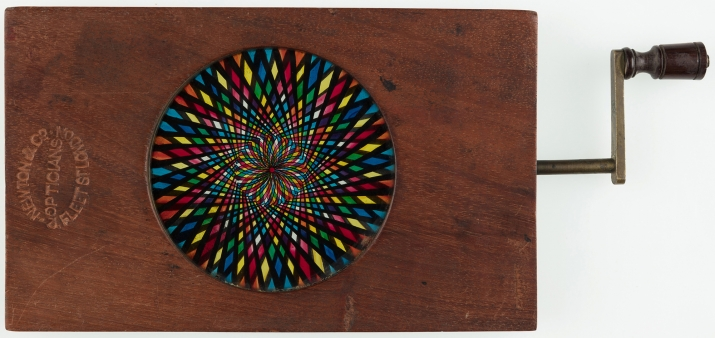 Automated timber and brass framed circular glass lantern slide hand painted kaleidoscope. Timber and brass handle operates secondary plate producing optical effect. Frame stamped with manufacturer's details and slide number inscribed on top edge in black