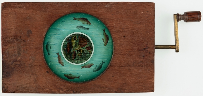 Automated timber and brass framed circular glass lantern slide featuring fish and other marine creatures. Timber and brass handle operates secondary plate allowing the fish to move.