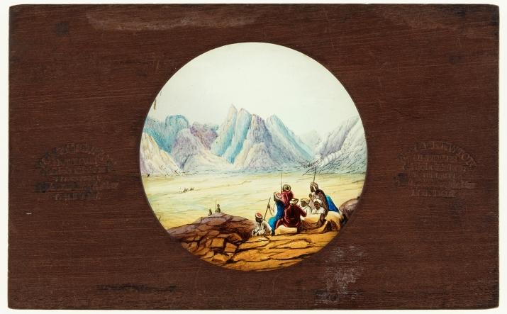 A timber framed, circular glass, static lantern slide featuring a hand painted Arabian scene, or possibly the Atlas Mountains of North Africa.