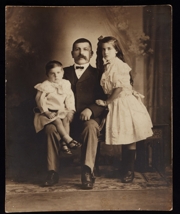 Studio portrait of resident and shopkeeper Swedish-born Hugo Knut Ljunggren (Youngein) with two of his children, Herbert and Jenny, c1910.