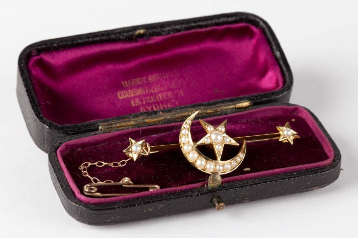A gold bar brooch (-1) with a star and crescent moon design set with pearls. Made by Hardy Bros, Sydney, circa 1886.