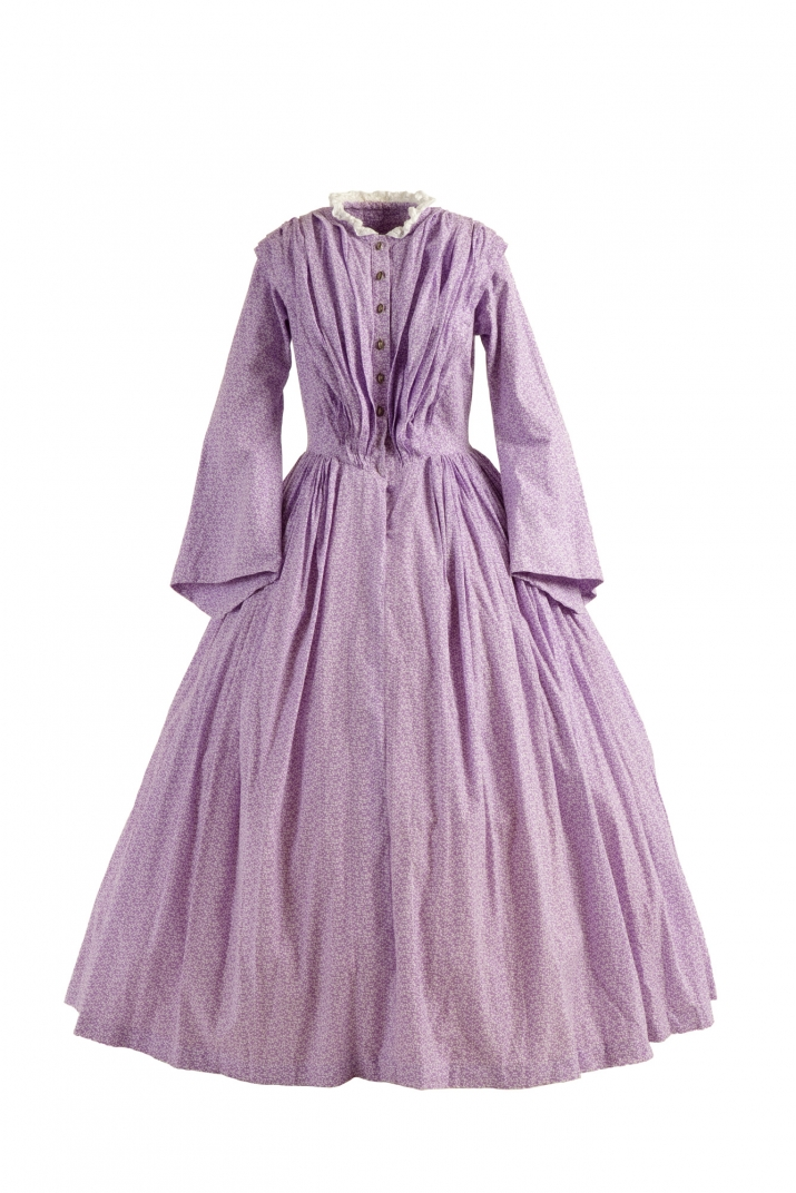 Mauve dress with plain, front-buttoning fitted bodice with a small, high collar, bell-shaped skirt worn over petticoats, and loose-fitting or frilled sleeves that could be rolled up.