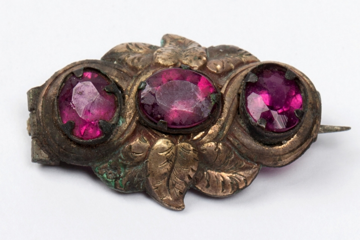 A delicate little metal brooch, only 2.5 cm wide, with three magenta-coloured faceted stones.