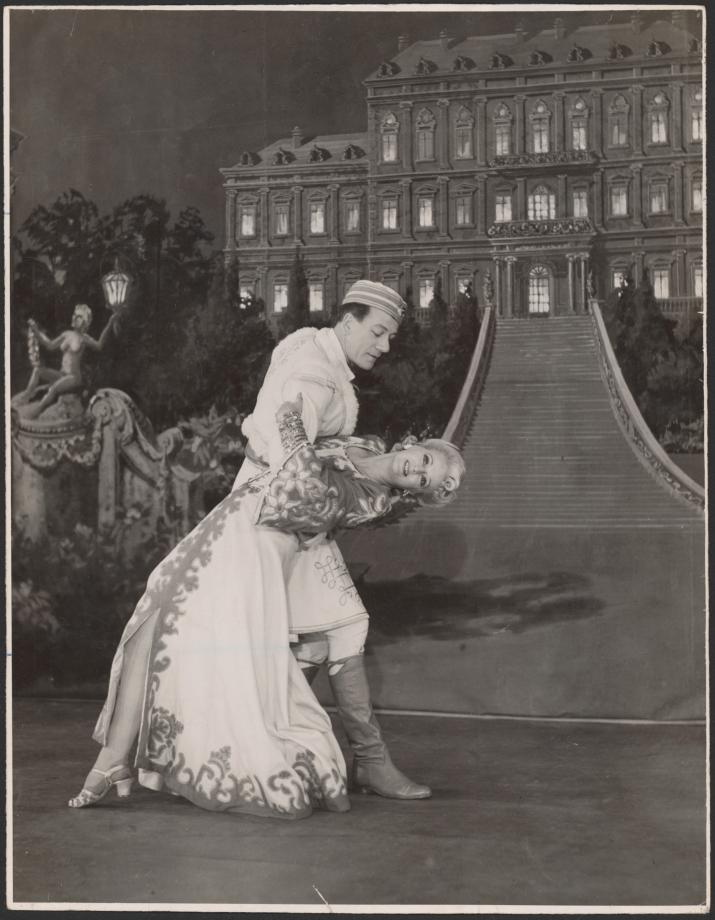 Studio shot of man holding woman in dramatic pose, both in costumes on set.