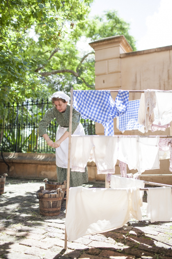 Woman dressed as convict washing clothes in sandstone courtyard with laundry hanging up around her.
