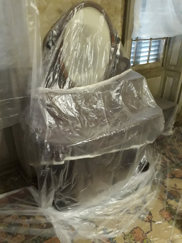 Furniture item draped in plastic.