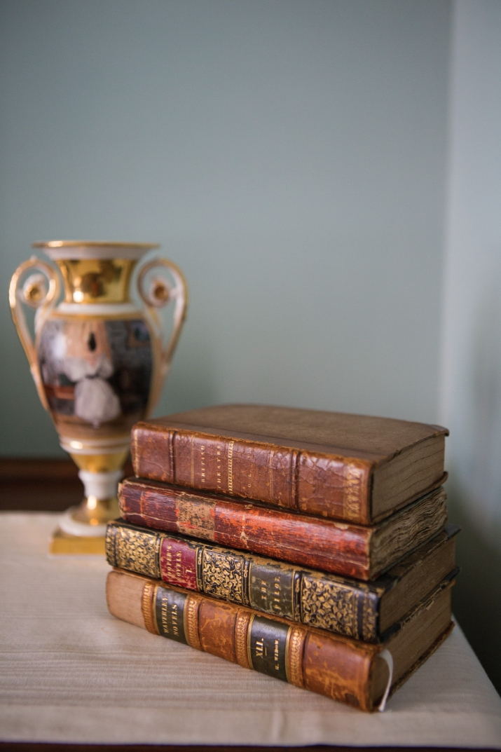 Stack of four old leatherbound books in front of two-handled vase.