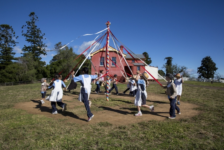 Students holding ribbons and dancing around the maypole outside the schoolhouse at Rouse Hill House & Farm.