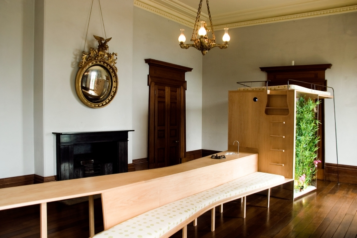 Long timber structure kitchen and seating structure in an ornate Georgian room