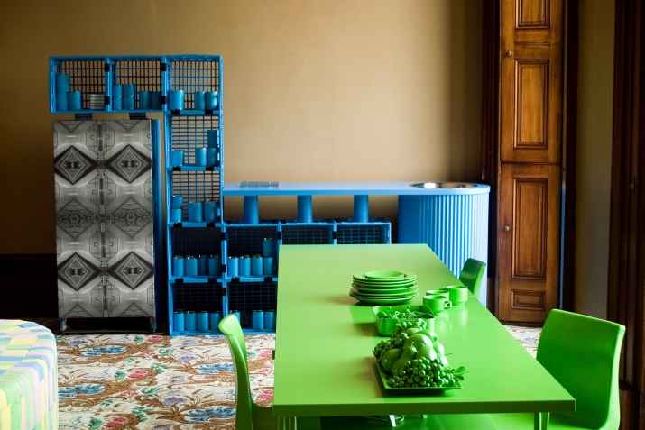 A green table with green plates and cutlery in front of a blue structure made from milk crates