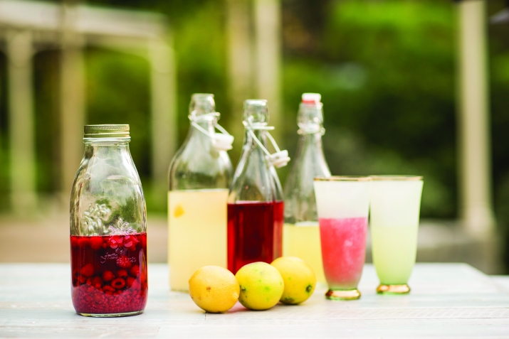 Group of bottled cordials of different colours with fruit and glasses.