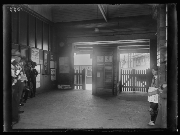Black and white photo of interior of station entrance way, looking out to street.