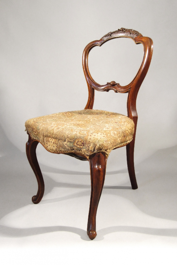 Wooden chair with curved frame and fabric seat.