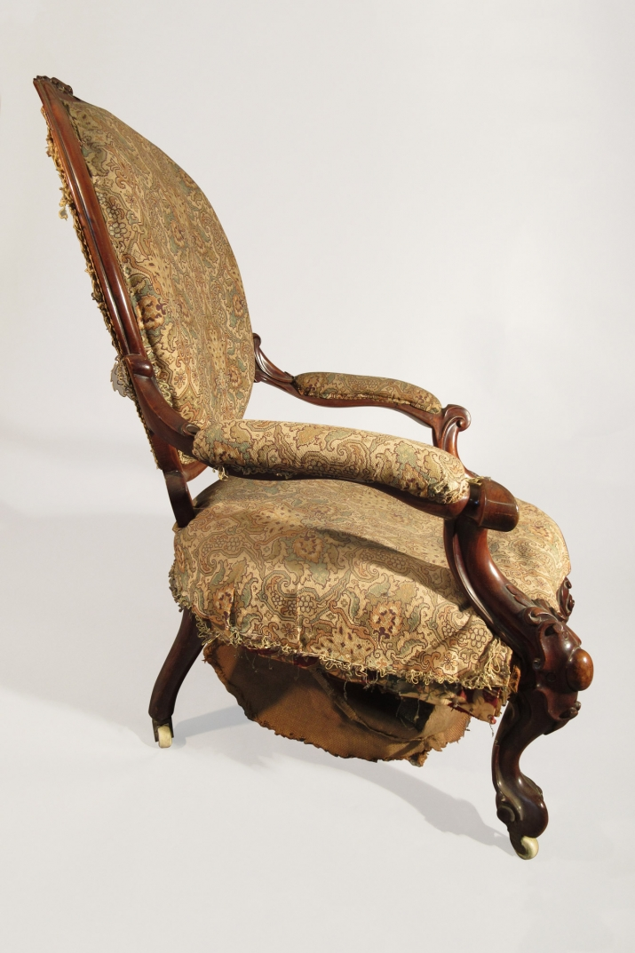 Wooden framed upholstered chair with arms showing damaged base.