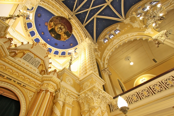 Looking up at ornately decorated domed ceiling space with blue and gold decorative features.