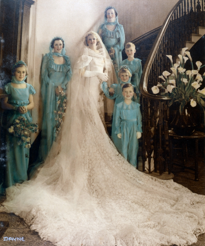 Colourised photo of woman in elaborate and lengthy wedding dress, flanked by 3 bridesmaids and 3 children.
