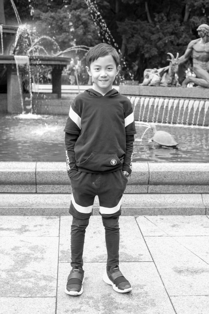 Black and white photo of young boy in sports gear in front of fountain.