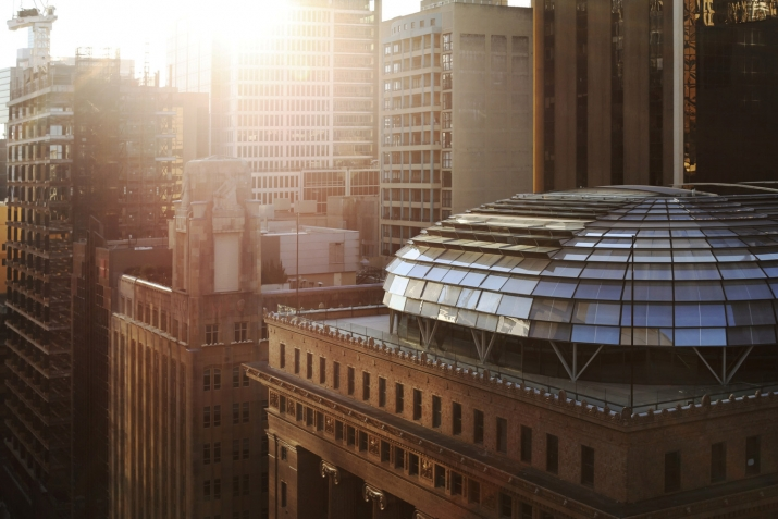 Sunlit dome on top of heritage building surrounded by other buildings.