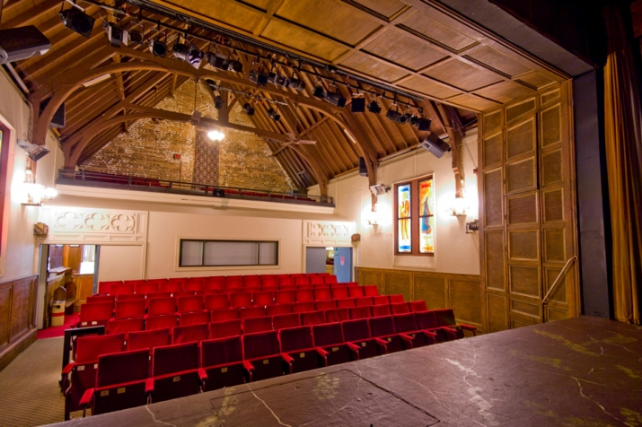 Looking into seating area from stage, with wooden rafters of exposed ceiling above.