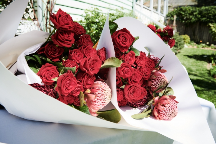 Two bouquets of red flowers and roses wrapped in white paper