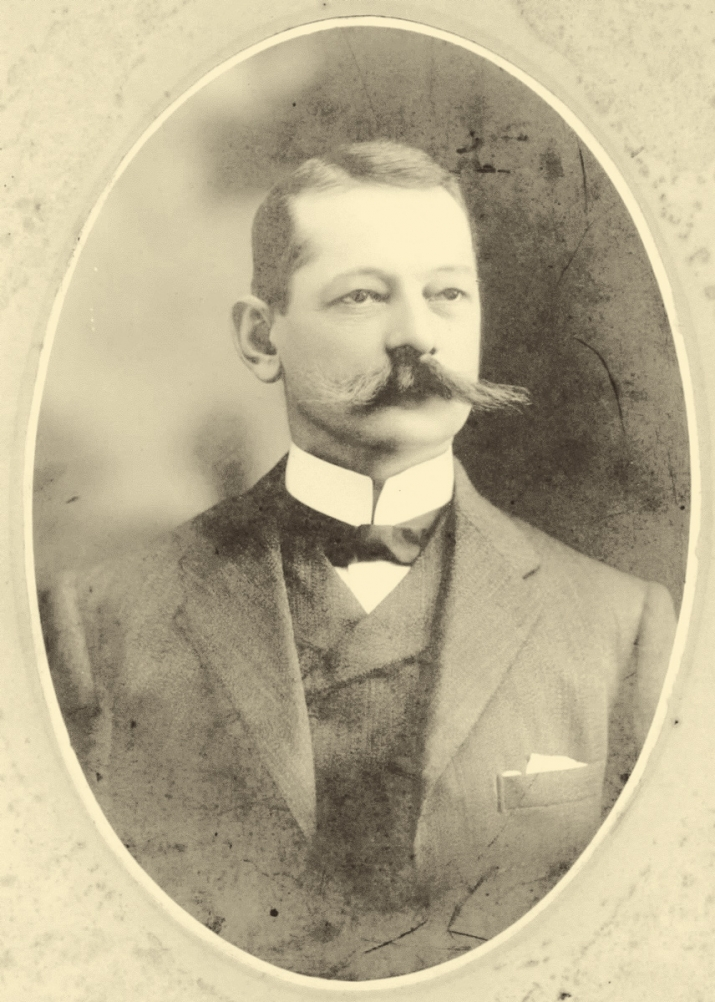 Faded photo of man with large handlebar moustache.