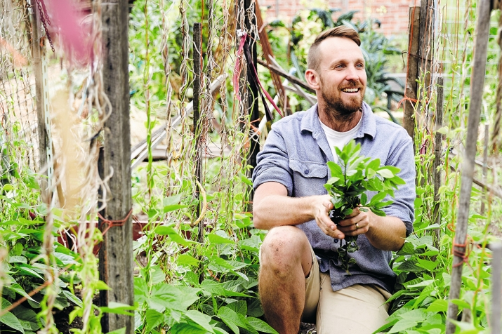 A picture of chef and River Cottage host Paul West kneeling in a kitchen garden