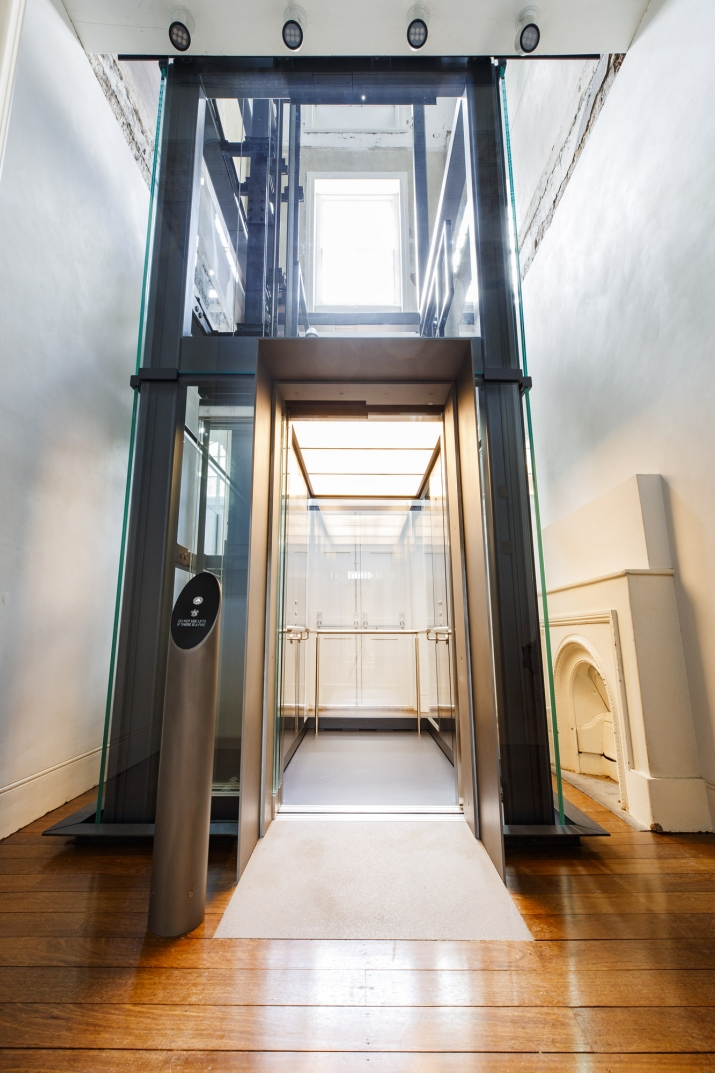 Wooden floored hall with glass lift installed.